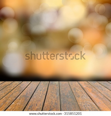 Old wooden deck table with a sparkling bokeh of party lights in the black background - stock photo