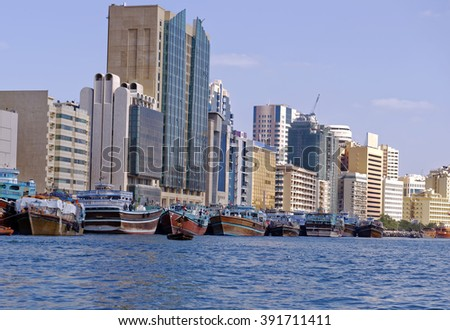 Old wooden dhows moored on Dubai Creek with modern office buildings in the background, Dubai City, United Arab Emirates