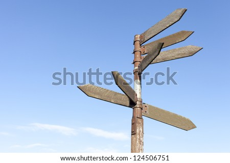 Old wooden direction signs against blue sky - stock photo