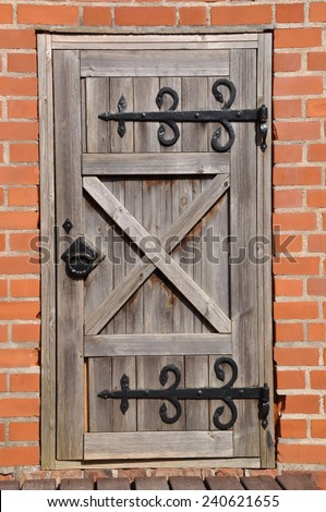 Old wooden door and red brick wall  - stock photo