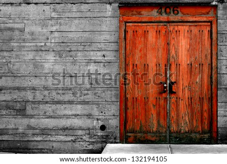 Old wooden door contrasted against dull concrete wall.