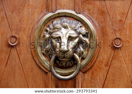 Old wooden door decorated with a lion head as a knocker - stock photo