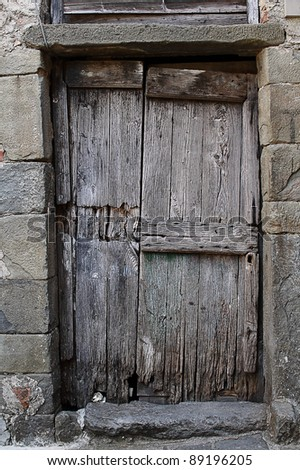 Old wooden door in a gray masonry wall, Italy - stock photo