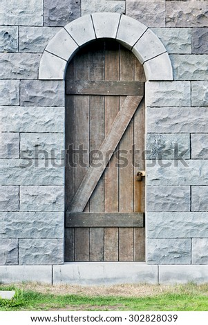 Old wooden door in a stone wall - stock photo