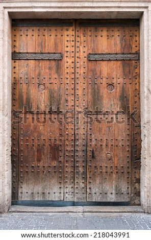 Old wooden door in an ancient stone building - stock photo