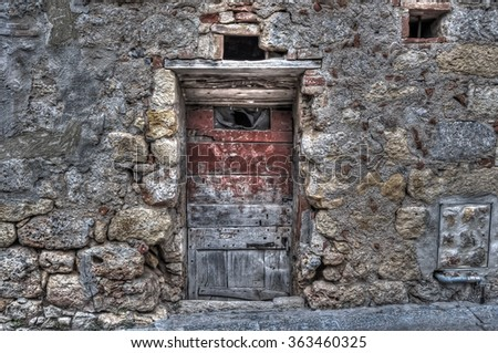 old wooden door in an old brick wall - stock photo