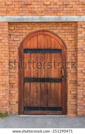 old wooden door in brick wall - stock photo