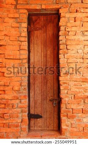 Old wooden door in brick wall background - stock photo