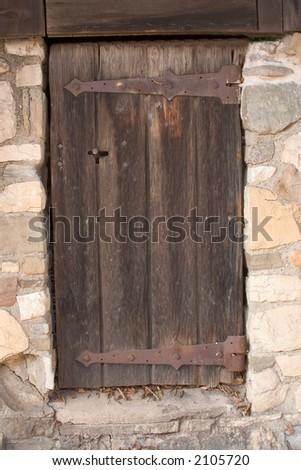 Old wooden door in stonewall - stock photo