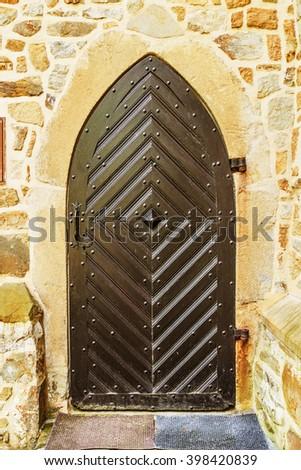 Old wooden door in the ancient beautiful building in Western Europe. - stock photo