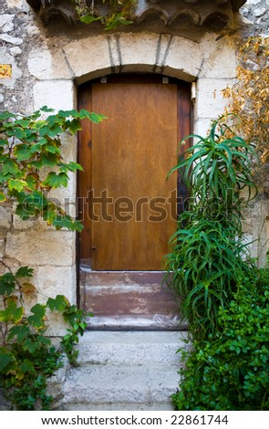 Old wooden door in the medieval city of Exe, France, which is a fortress, built on cliff-side hill