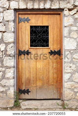 Old wooden door in the stone wall. - stock photo