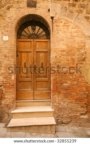 Old wooden door in tuscany - stock photo