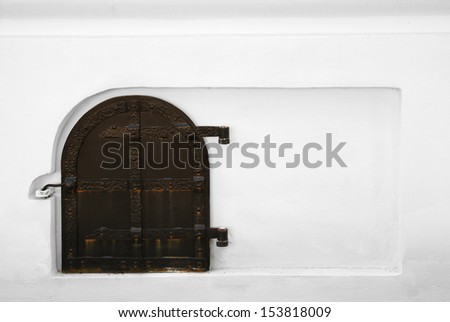 Old wooden door is hinged on white wall. Ancient entrance is armored with rusty iron stripes. - stock photo