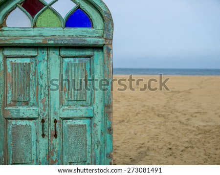 old wooden door leading to a beautiful beach - stock photo