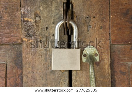Old wooden door locked with a Padlock.
