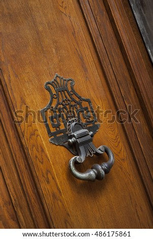 Old wooden door of a French mansion and wrought iron knocker