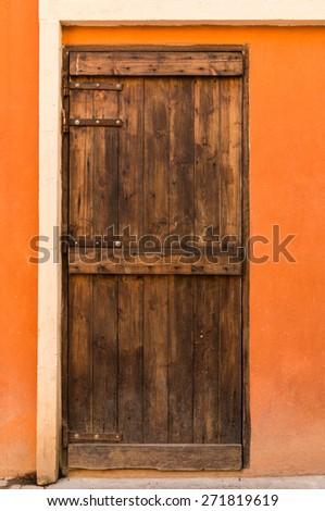 Old Wooden door on orange wall  background - stock photo