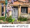Old Wooden door to a Traditional English Village Cottage with Climbing Wisteria on the Wall - stock photo