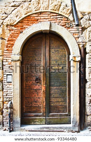 Old wooden door with a metal knocker and letter slot - wonderful texture. The door has little metal studs. On the side, there is a modern door bell and intercom. - stock photo