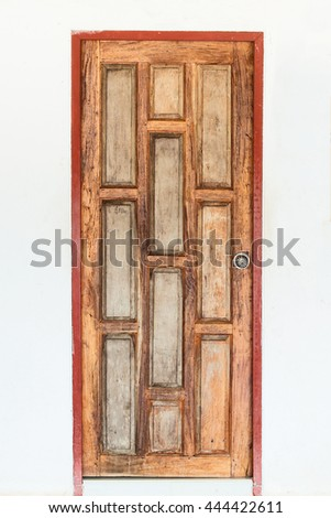 Old wooden door with a white wall.