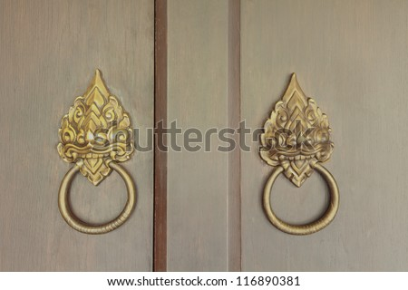 Old wooden door with brass lion head handle in Thai style - stock photo