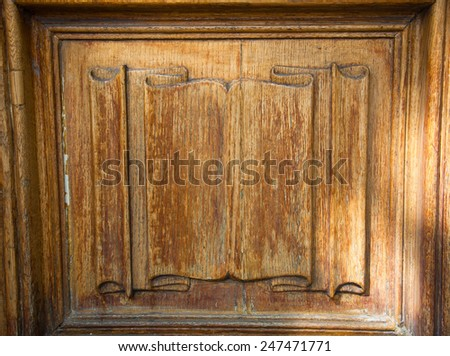 """Old wooden door with carved """"scroll banner"""". - stock photo"""