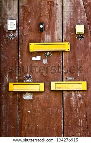 Old wooden door with doorbells and mail slots in Lisbon - stock photo