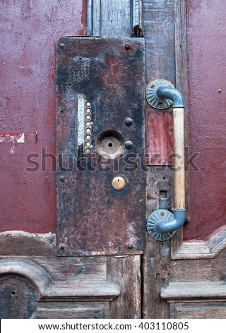 Old wooden door with flat buttons and vintage handle - stock photo