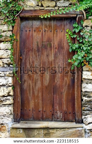 Old Wooden Door with forging nails and handle. Background and Texture for text or image. - stock photo