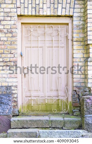 Old wooden door with grating in a brick wall and stone stairs - stock photo