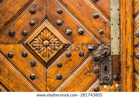 Old wooden door with handle decorated with flower carved in wood