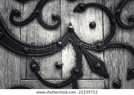 Old wooden door with iron adornments - stock photo