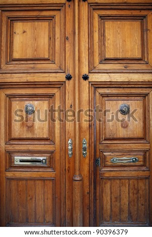 Old wooden door with ornaments of an antique building - stock photo