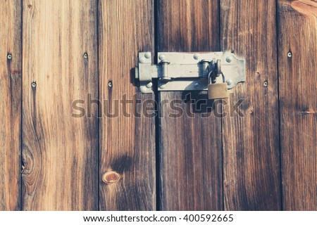 old wooden door with padlock and metal latch - vintage look - stock photo