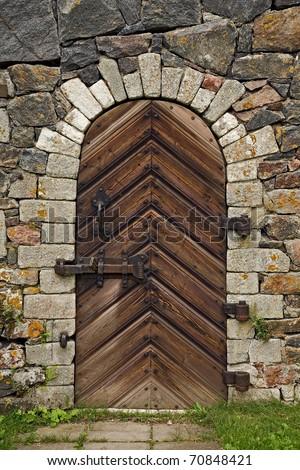 Old wooden door with rusty hinges - stock photo
