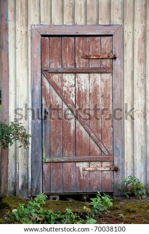 Old wooden door with stone step - stock photo