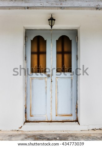 Old wooden door with  White cement wall - stock photo