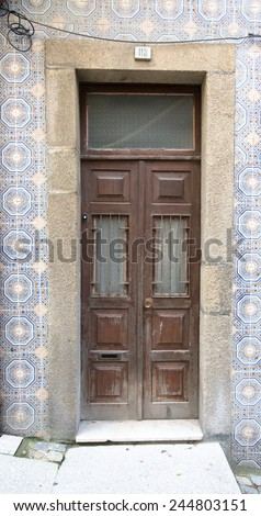 Old wooden door with window on the wall with ceramic tile.