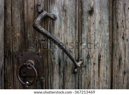 old wooden door with wrought iron handle - stock photo