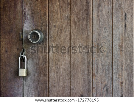 Old wooden doors are locked with a padlock and doorknobs - stock photo
