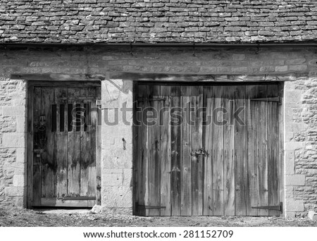 Old wooden doors in a stone built building - stock photo