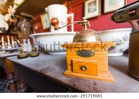 Old wooden dusty coffee grinder on a wooden table in an antique shop. - stock photo