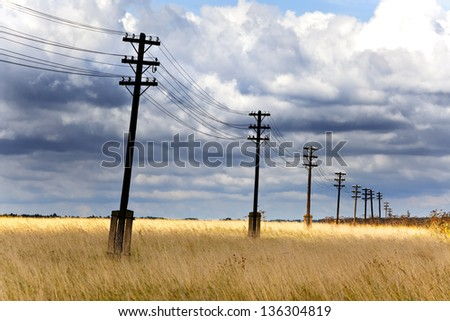 Old wooden electric pillar in the field - stock photo