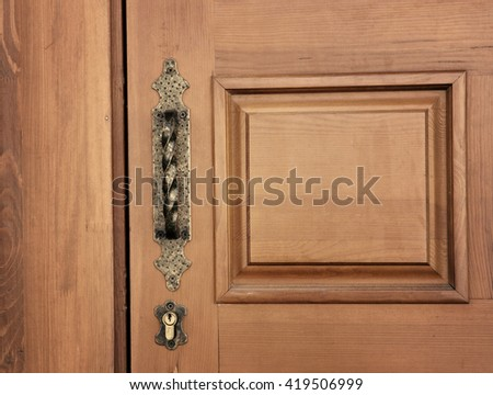Old wooden entrance door with forged door handle and lock - stock photo