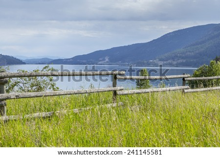 Old Wooden Farm Fence at Scenic Lake Shore - stock photo