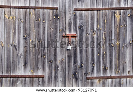 Old wooden farm rural building doors locked with padlock. Background of old architecture. - stock photo