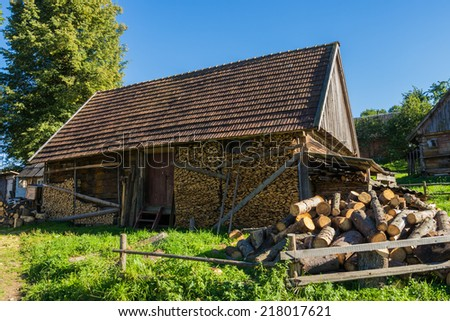 Old wooden farmhouse in the Carpathians with the wood in the yard. - stock photo