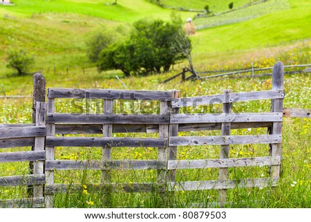 Old wooden fence and gate at a farm in the mountains - stock photo