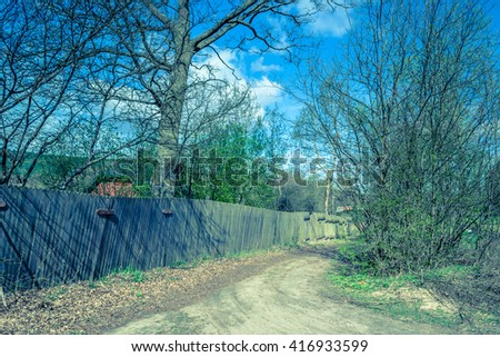 Old wooden fence from wooden planks standing at rural road - stock photo